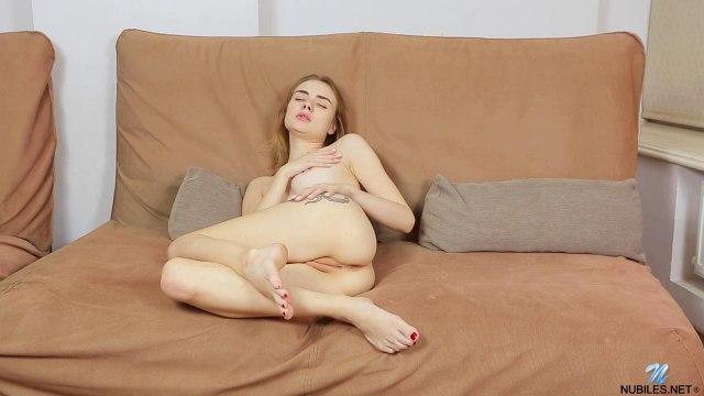Девушка лежит на диване и трогает рукой соски и мягкий клиторок #9